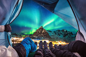 Group of climber are inside camping with aurora borealis over mountain at Sakrisoy village