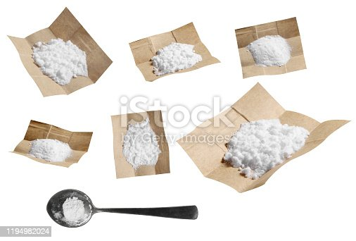 Group of cocaine in paper and spoon isolated on white background