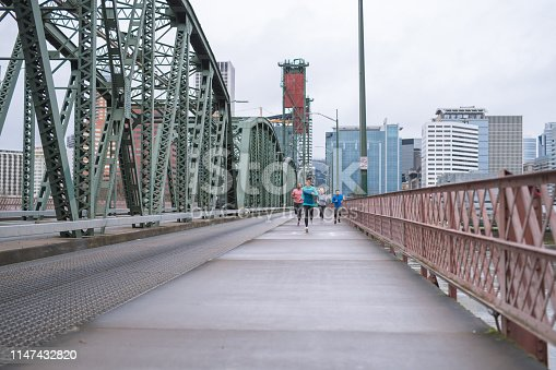 A co-ed group of four runners jogs across a city bridge on a training run. They all look enthusiastic and cheerful. An ethnic woman is in the front. City buildings are in the background and the river is below.
