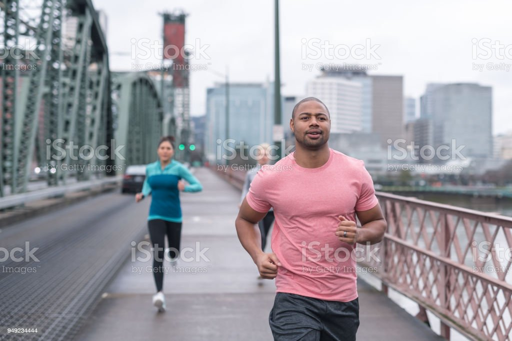 A group of co-ed runners goes for a training run in the city stock photo