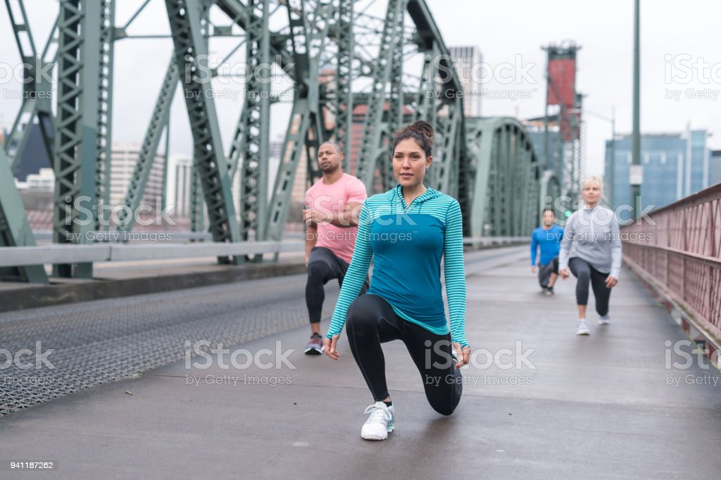 A group of co-ed runners stretches out before a training run in the city stock photo