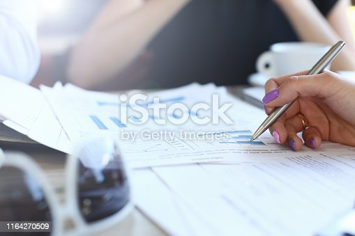 Focus on business woman hand with perfect manicure holding pen and pointing to important papers. Corporate workers discuss charts and graphs with different business information