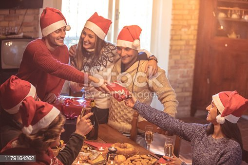 1064325668istockphoto Group of college friends having fun during Christmas holidays and giving xmas presents to each other. Millennials friendship concept. Young people with red Santa hats celebrating x-mas. 1179164262