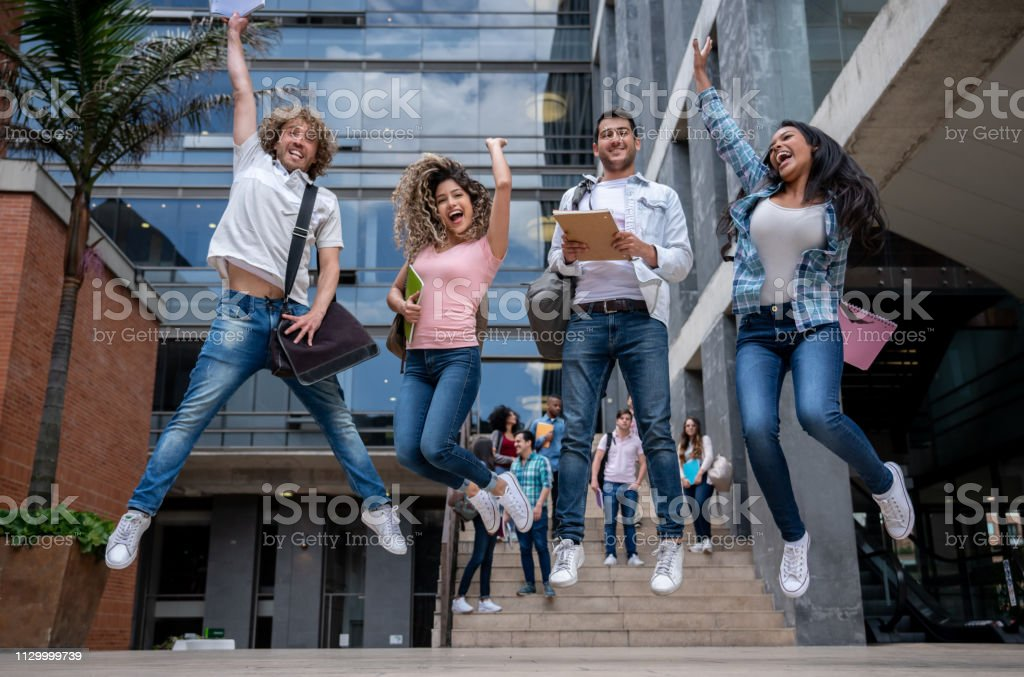 Group of college friends umping very excited holding their notebooks...