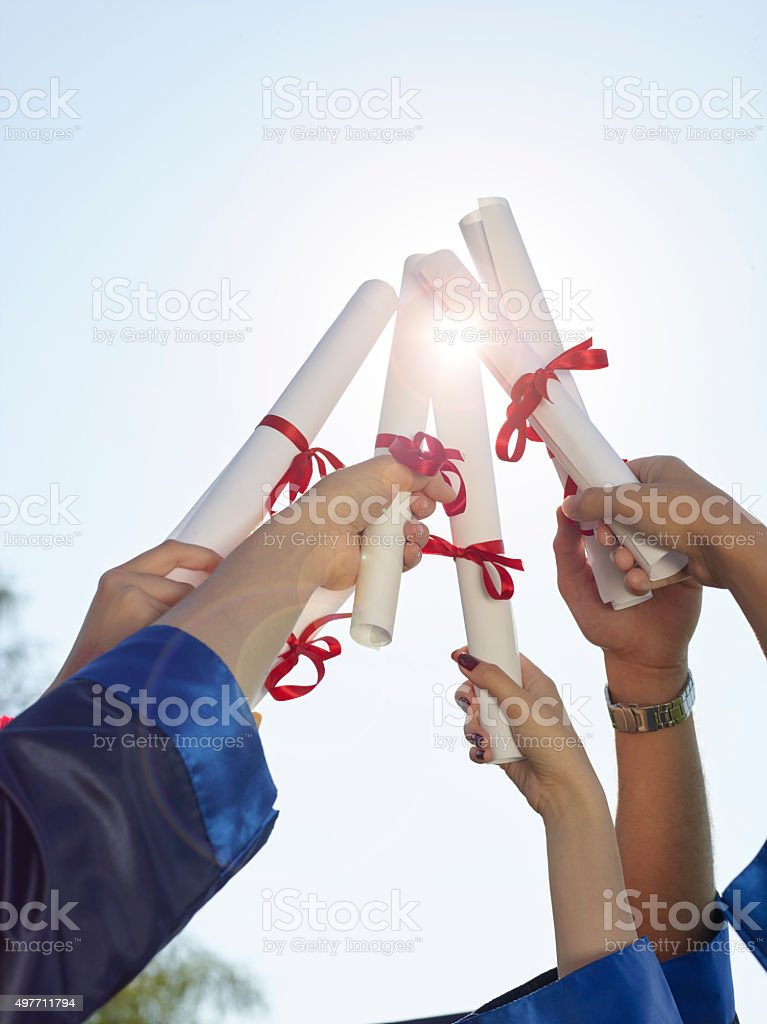 Group of college graduates holding diplomas in air stock photo