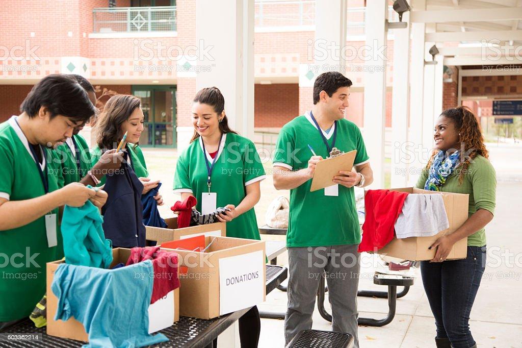 Grupo de estudiantes universitarios voluntarios recolectar ropa donaciones. Caridad. - foto de stock