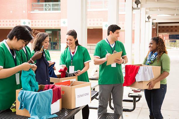 grupo de estudiantes universitarios voluntarios recolectar ropa donaciones. caridad. - ayuda humanitaria fotografías e imágenes de stock