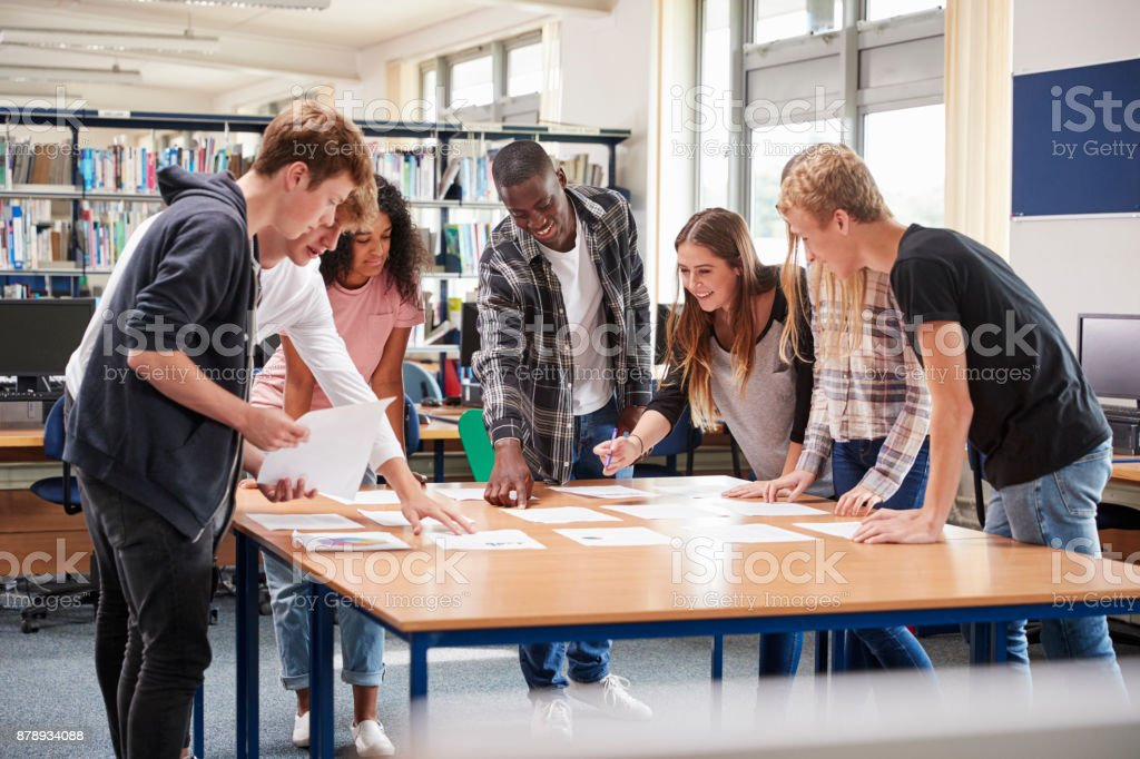 Group Of College Students Collaborating On Project In Library stock photo