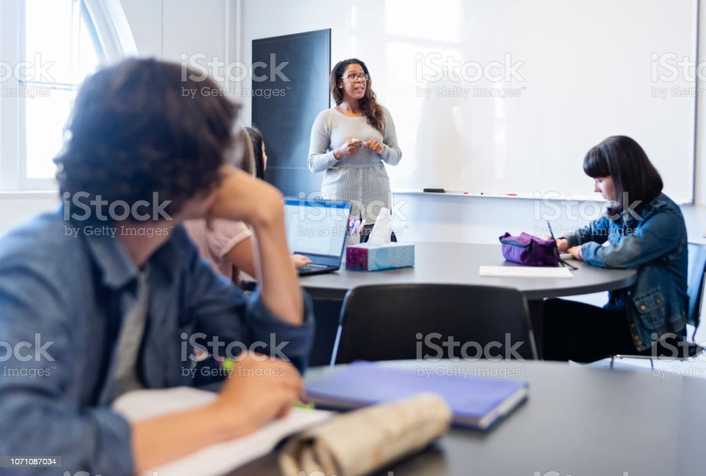 Group of College students listening to woman teacher in classroom. stock photo