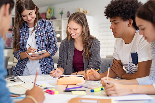 Happy team of high school girls and guys studying together and laughing. Group of multiethnic classmates smiling and studying while sitting in university library. Group of young people sitting at table working on school assignment.