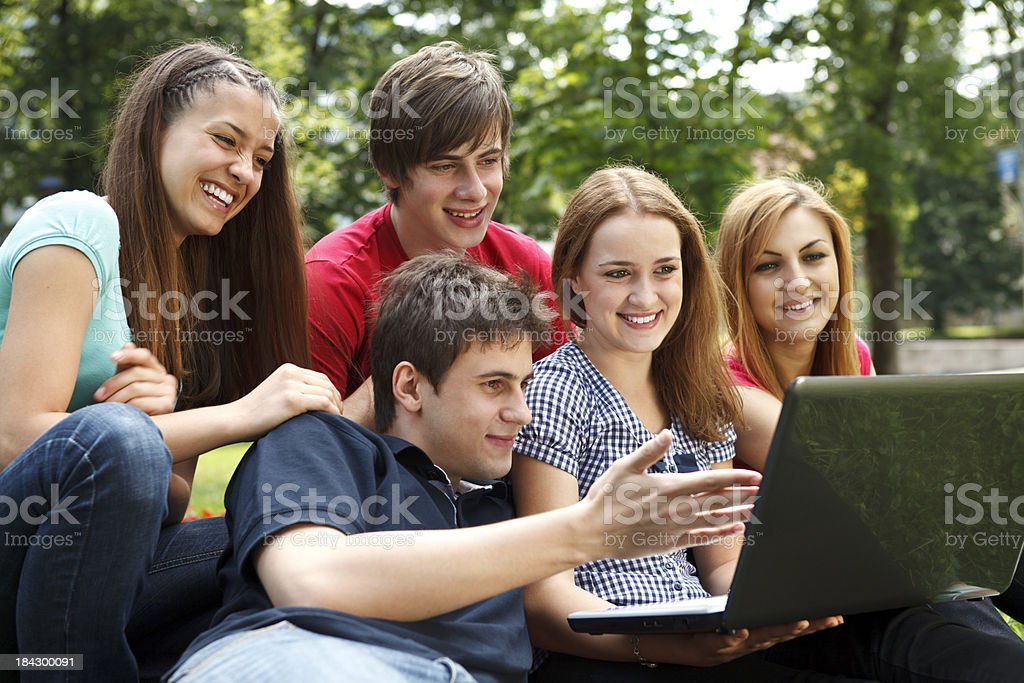 Group of college students using laptop outdoors royalty-free stock photo