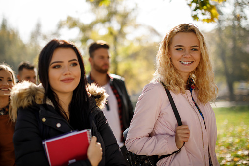 872670290 istock photo Group of college students walking on university campus 1019565146