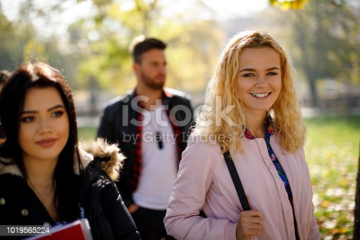 872670290istockphoto Group of college students walking on university campus 1019565224