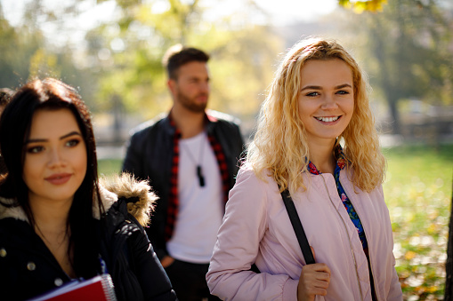 872670290 istock photo Group of college students walking on university campus 1019565224