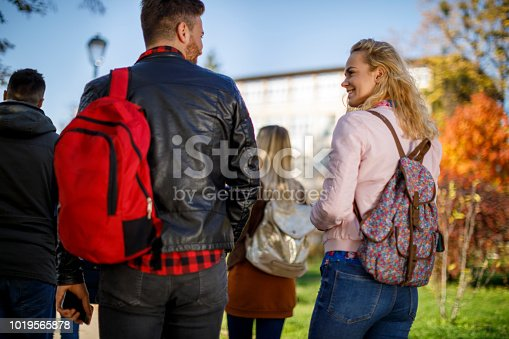 872670290istockphoto Group of college students walking on university campus 1019565878