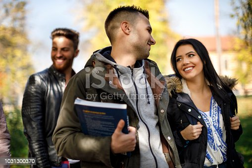 824257318 istock photo Group of college students walking on university campus 1031300370