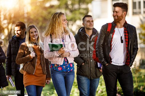824257318 istock photo Group of college students walking on university campus 1031303080
