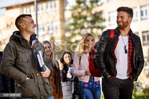 824257318 istock photo Group of college students walking on university campus 1031303162