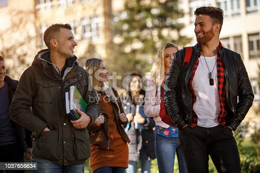 872670290istockphoto Group of college students walking on university campus 1037656634