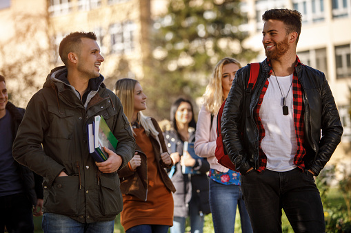 872670290 istock photo Group of college students walking on university campus 1037656634