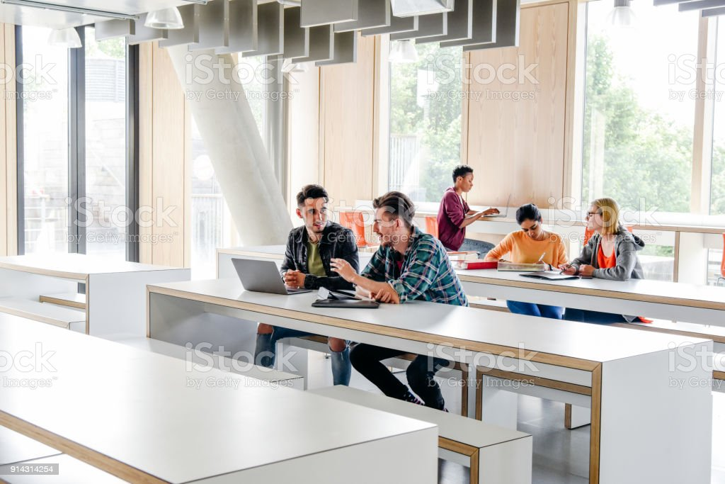 Group Of College Students Working At Desks In Modern Classroom Stock