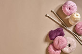 A group of colored balls of yarn and knitting needles on a beige background. Top view. Still life. Copy space. Flat lay