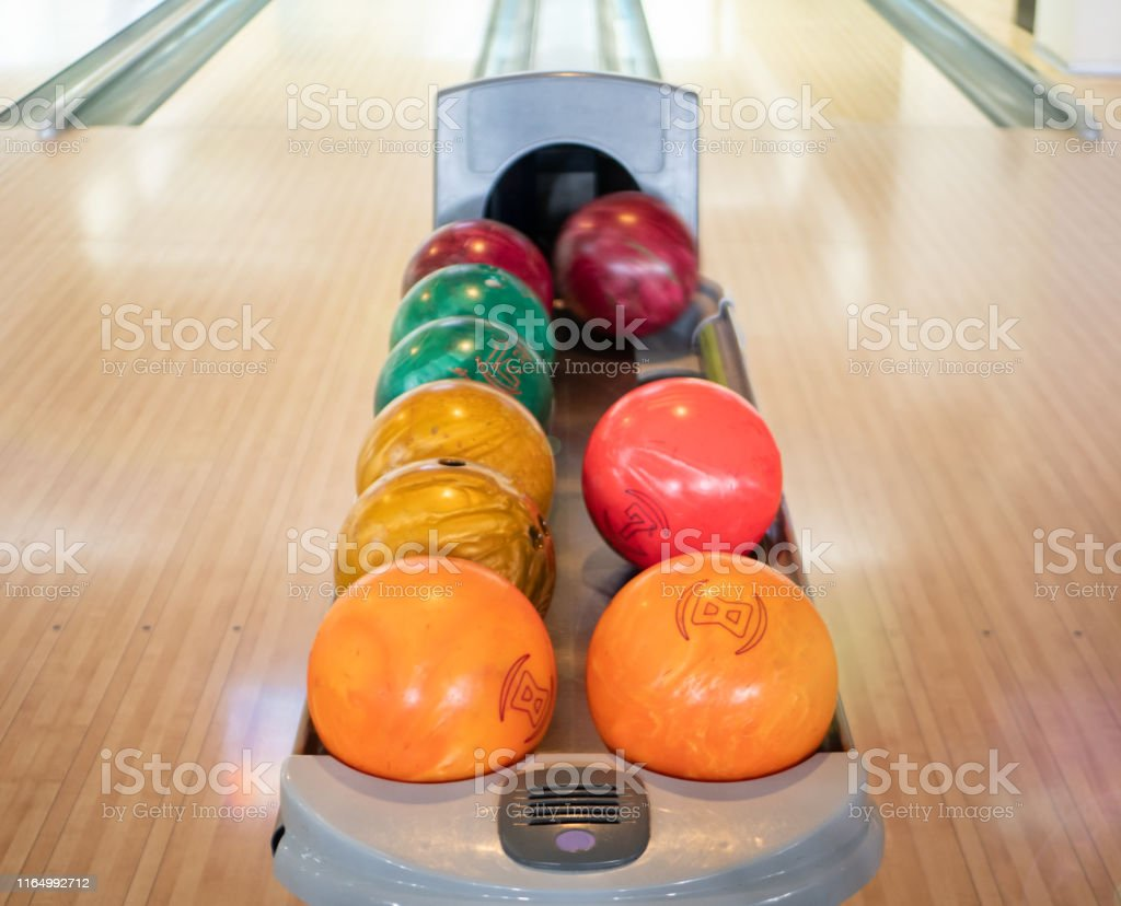 group of colorful balls at bowling club. nobody in the frame. family...