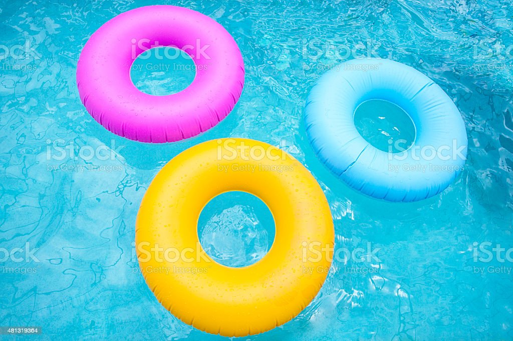 Group of colorful inflatable tubes floating in a swimming pool stock photo