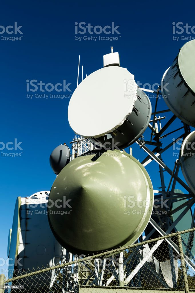 Group Of Communication Receivers Behind Fence With Blue Sky stock photo
