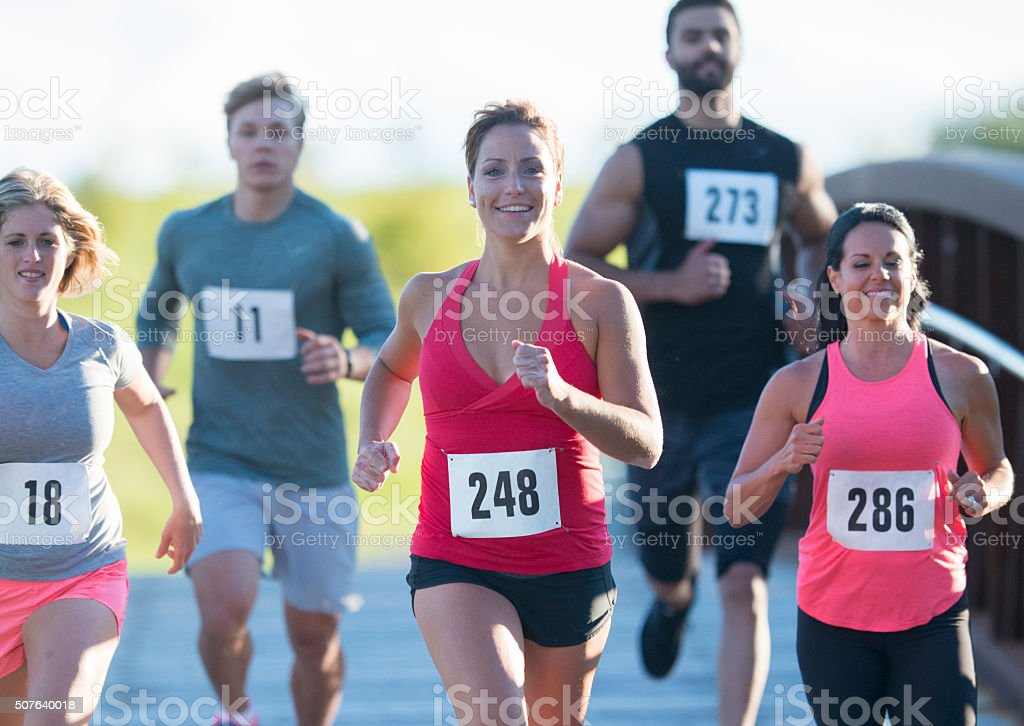 A group of competetive runners racing. stock photo