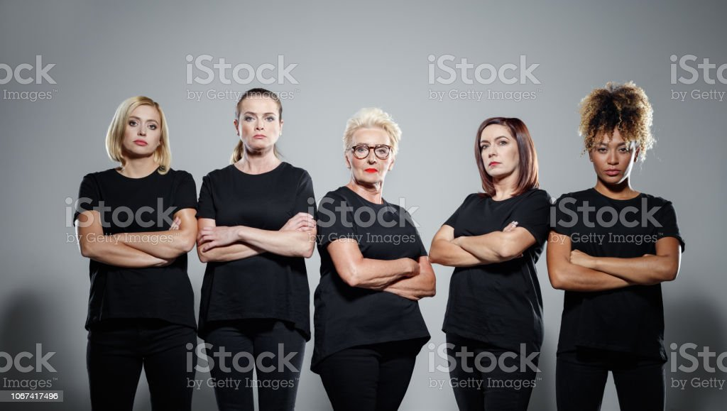 Group of confident women protesting Group of displeased women wearing black clothes, standing with arms crossed against grey background. Studio shot. Activist Stock Photo