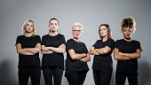 Group of displeased women wearing black clothes, standing with arms crossed against grey background. Studio shot.