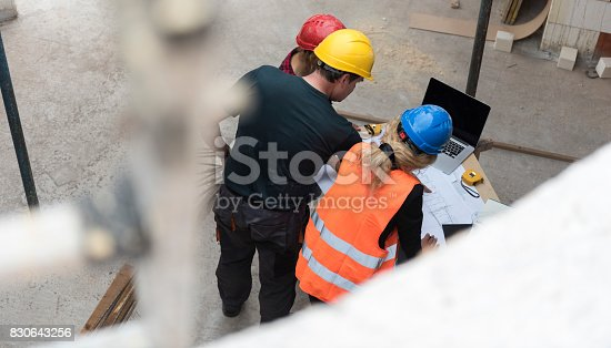 521012560istockphoto Group of construction workers reviewing plans 830643256