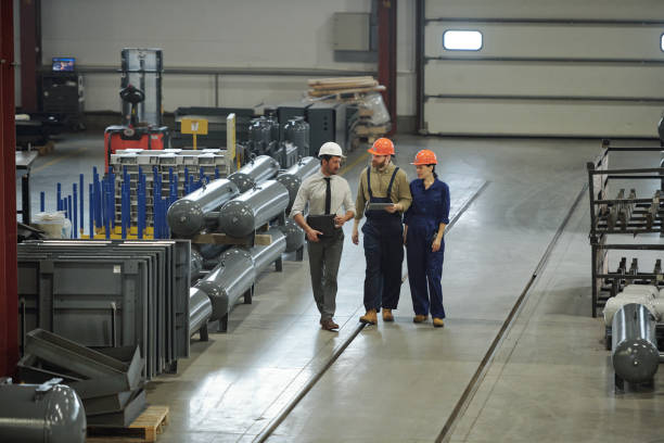 Group of contemporary professional technicians in workwear moving along workshop stock photo