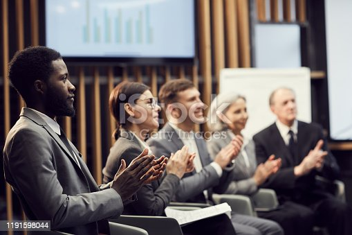 511305456 istock photo Group of content inspired multi-ethnic business people sitting in row and thanking speaker with applause after presentation at conference 1191598044
