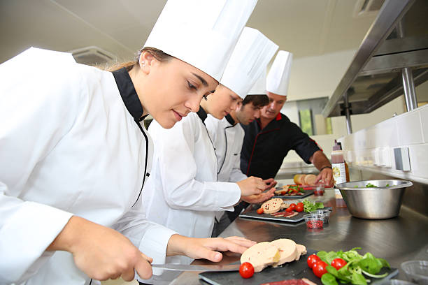 group of cooks working with chef in kitchen - food and drink stock photos and pictures