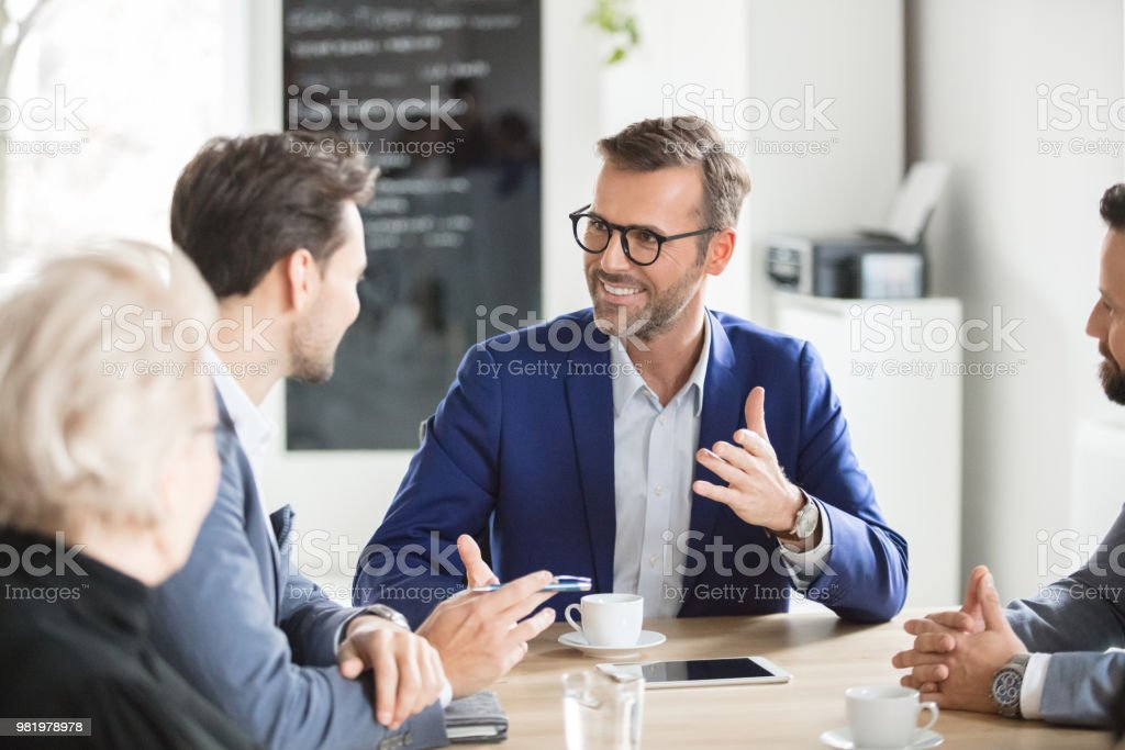 Group of corporate professionals having meeting Happy businessman taking with colleagues in boardroom meeting. Group of corporate professionals during conference meeting. Adult Stock Photo