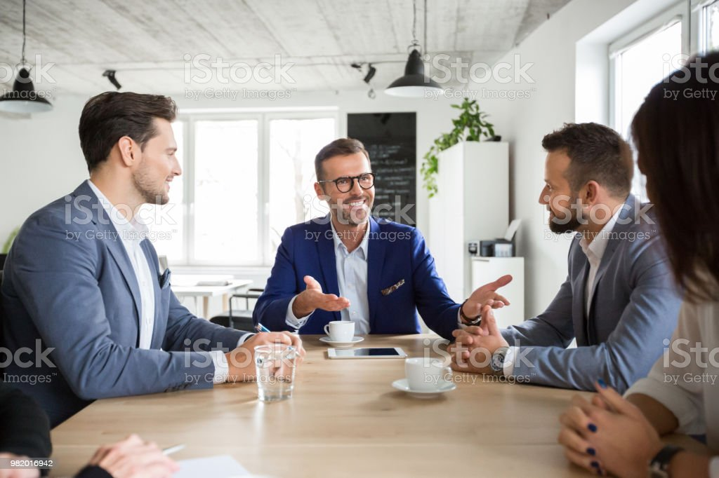 Group of corporate professionals in meeting Happy mature businessman in discussion with colleagues in boardroom meeting. Group of corporate professionals during conference meeting. Adult Stock Photo