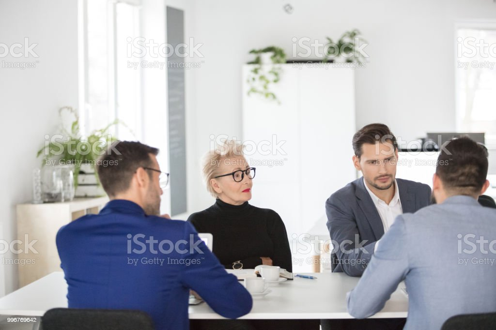 Group of corporate professionals in meeting Business people having a meeting in office. Group of corporate professionals sitting around conference table and discussing new project. Active Seniors Stock Photo