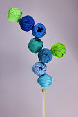 group of cotton balls yarn in the shades of blue and green  in balance on knitting needle, lilac background