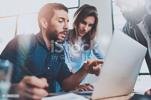 istock Group of coworkers sitting at the wooden table and working together on new startup project in modern loft office.Horizontal.Blurred background. 912665030