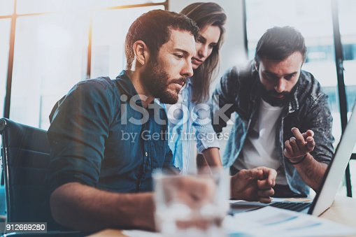 912969272istockphoto Group of coworkers sitting at the wooden table and working together in modern office.Horizontal.Blurred background. 912669280