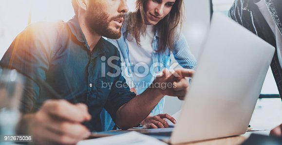 istock Group of coworkers sitting at the wooden table and working together on new startup project in modern loft office.Horizontal.Blurred background.Cropped. 912675036