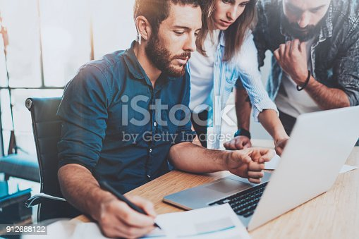 istock Group of coworkers sitting at the wooden table and working together in modern loft office.Horizontal.Blurred background. 912688122