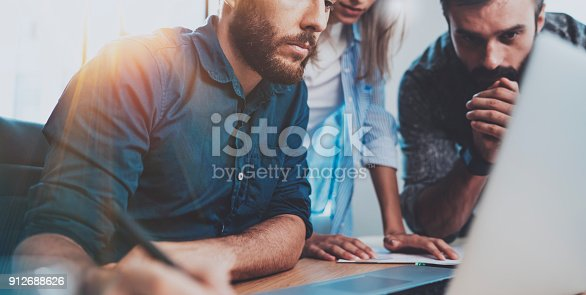 912969272istockphoto Group of coworkers sitting working together on new startup project in modern loft office.Horizontal.Blurred background.Cropped. 912688626