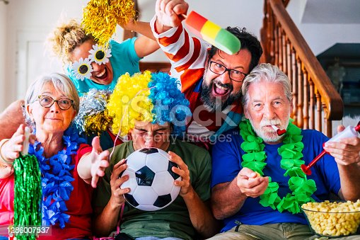 Group of crazy and coloured football supporter celebrate and exult during the match - mixed ages of caucasian people family and friends enjoy sport support activity together having fun and go for team victory