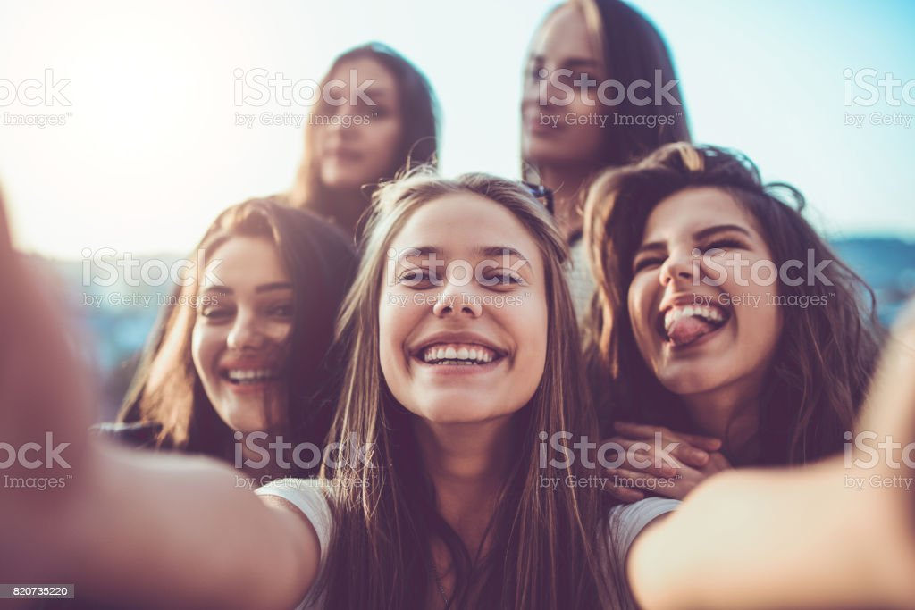 Group of Crazy Girls Taking Selfie and Making Faces Outdoors stock photo