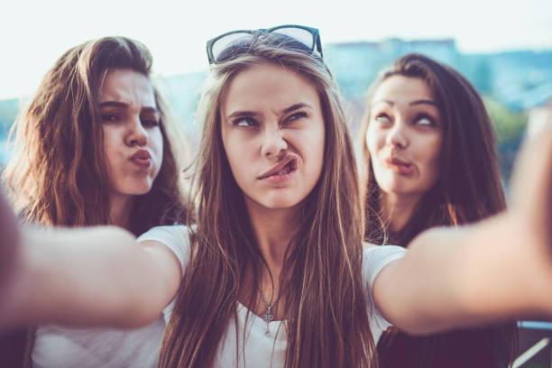 grupo de chicas locas selfie y haciendo caras al aire libre - poner caras fotografías e imágenes de stock