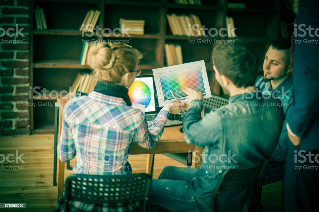 group of creative designers discuss the color palette in a moder stock photo