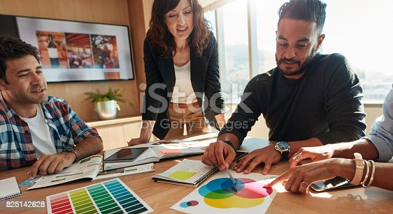 848290020istockphoto Group of creative designers discuss the color palette 825142628